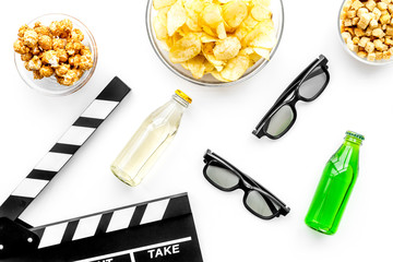 Crisp, popcorn, rusks for watching film. Clapperboard and glasses on white background top view
