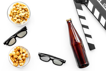 Popcorn, rusks for watching film. Clapperboard and glasses on white background top view copyspace