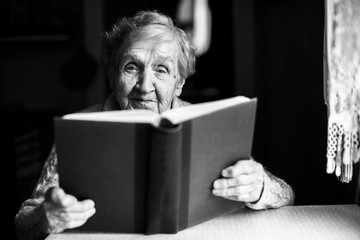 Elderly woman reads the book at the table. Black-and-white photo.
