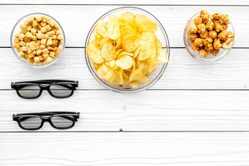 Cinema food. Crisp, popcorn, rusks near glasses on white wooden background top view copyspace