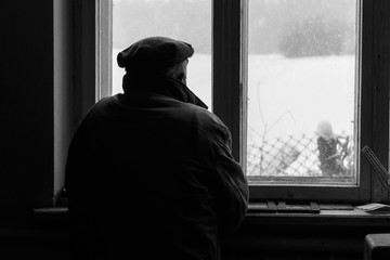 Lonely senior man looking out the window