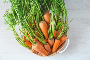 Wicker basket with ripe carrots on table