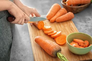 Woman cutting carrot on table, closeup