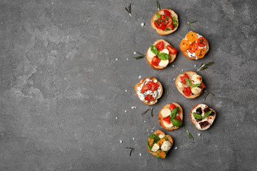 Tasty bruschettas with tomatoes on grey background