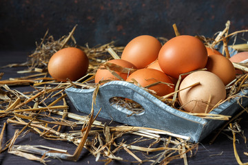Eggs of brown chicken on a wooden background with straw with copy space in rustic vintage style