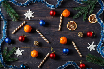 Christmas background with tangerines, colored balls, toys, bells, sweets