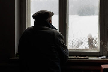 Lonely man looking out the window