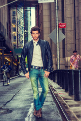 European businessman traveling in New York. Wearing black leather jacket, white undershirt, blue jeans, brown boot shoes, a young guy with beard walking on narrow wet street after raining, .