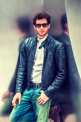 Man Spring/Autumn Casual Fashion. Young guy with beard, wearing black leather jacket unbuttoned, blue jeans, sunglasses, leaning against silver metal wall, smoking cigarette, relaxing, thinking..