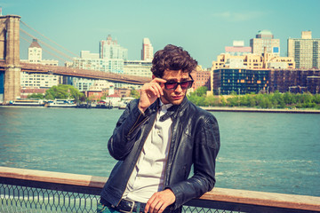 European man traveling in New York. Wearing leather jacket, holding sunglasses, a guy with beard standing by river, narrowing eyes, looking over glasses frame, watching away. Brooklyn on background. .