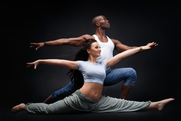 Black man and white woman in a beautiful dance position on a black background.