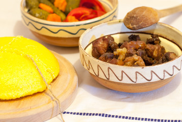 romanian traditional winter season meal with polenta mamaliga fried pork scraps and pickled vegetables