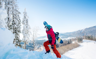 Shot of a male snowboarder carrying his board walking in the mountains on sunny winter day copyspace active sports lifestyle recreation seasonal people
