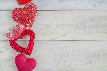 various red hearts on white rustic background with copy space