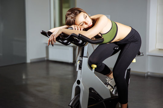 Portrait of exhausted woman spinning pedals on exercise bike