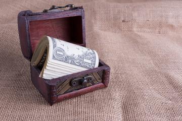 One dollar bills in wooden chest on burlap background