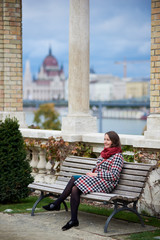 Nice girl sits alone on a bench near the columns on a blurred background of the architecture of the city of Budapest. Autumn in the city