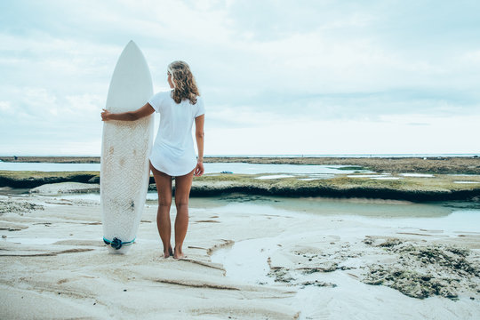Woman Standing on Sand Beach With Surfboard