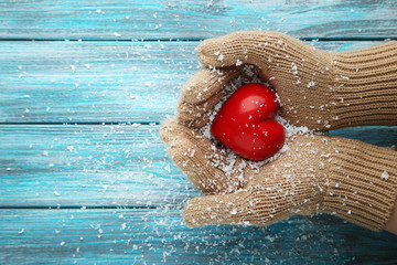 Hands in beige gloves holding red heart