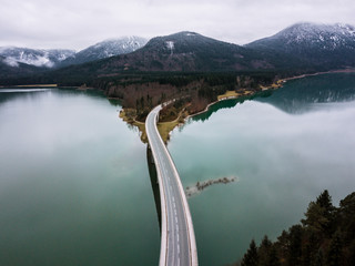 Aerial shot of lake Sylvenstein and it's bridge on a cloudy autumn day with mountains in in background