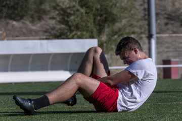 Footballer sitting on the grass for an injury