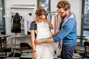Young woman client fitting wedding dress with man tailor standing at the sewing studio