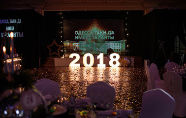 New Year's decorations of a festive banquet with golden stars, glass shiny balls and green branches of a Christmas tree