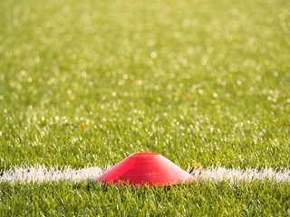 Bright red plastic cone on painted white line of soccer field. Plastic football green turf playground