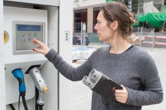 Frau waehlt Ladevorgang fuer Elektoauto aus
