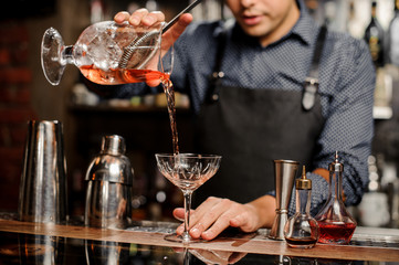 Bartender pours sweet cocktail in bocal