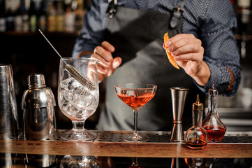 Bartender is going to spray an orange peel in cocktail glass