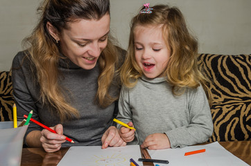 Young beautiful mother with her daughter draw with colorful pencils on paper, happy family
