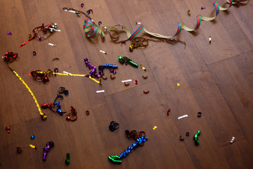 Shot of a wooden floor after a party celebration with party poppers and confetti