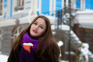 Street portrait of fabulous young woman wearing purple knitted scarf and holding cup of tea