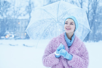 Outdoor portrait of young beautiful happy smiling girl walking in snow-covered street. Model wearing trendy winter pink faux fur coat, blue beanie hat, gloves, holding transparent umbrella. Copy space