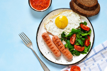 Homemade breakfast: egg, grilled sausage, vegetables, salad on a blue, concrete background.