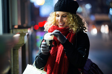 Beautiful young woman drinking coffee in the street at night.
