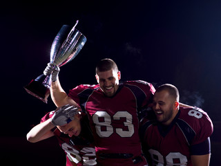 american football team with trophy celebrating victory