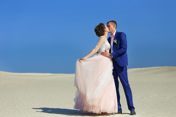 Young wedding couple on beautiful sand dune with wives on sea