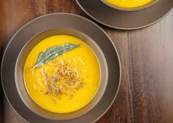 pumpkin soup with sage leaves in brown ceramic soup plate.
