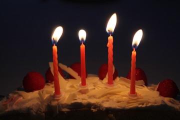 Lit candles on birthday cake with dark background.