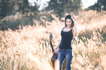 Beautiful young girl carrying her guitar through the golden wheat field