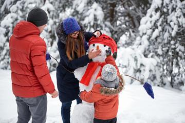 winter fun. a girl, a man and a boy making a snowman.