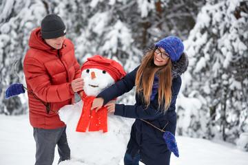 winter fun. a girl and a man making snowballs.