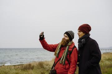Tourists taking selfie on beach