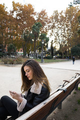 Woman with smartphone on park bench