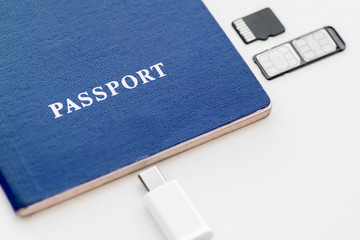 Blue Passport with sim card, memory card and usb cable on a white background