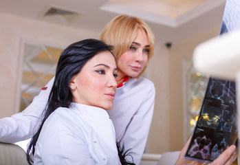 Female Doctors looking at a tomography x-ray picture