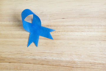 Blue ribbon on wood background