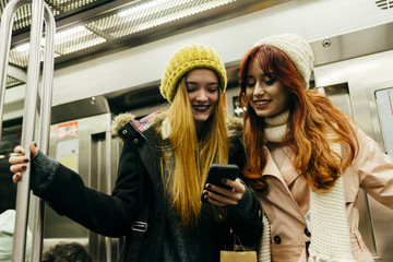 Cheerful women using phone in subway